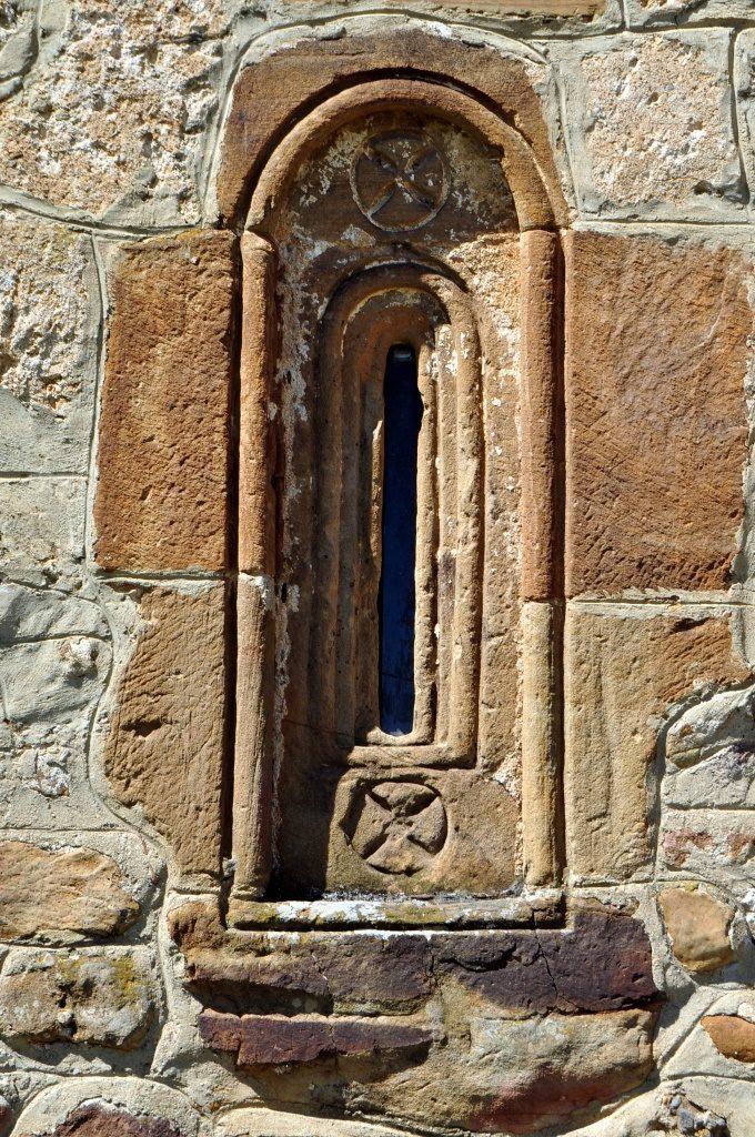 Puente Almuhey. Ventanita en la cabecera de la esrmita de Las Angustias. Tiene grabado el símbolo de los Caballeros Hospitalarios de San Juan de Jerusalén, después Orden de Malta