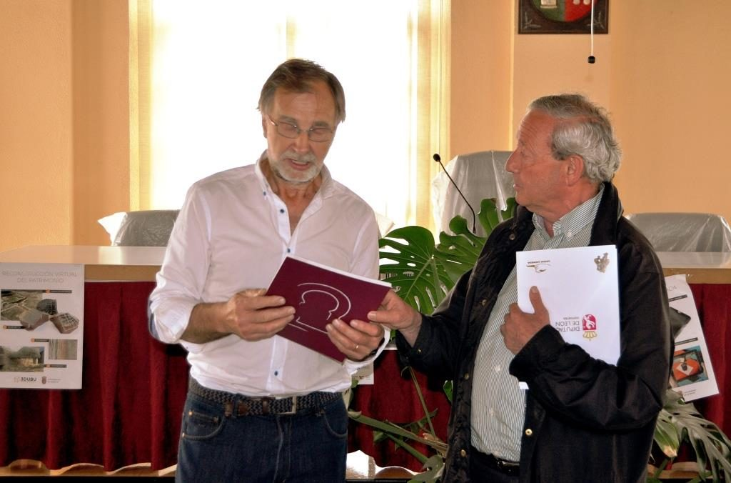 El alcalde de La Ercina, Ignacio Robles, y el presidente de Promonumenta, Marcelino Fernández, intercambian sus respectivas publicaciones.