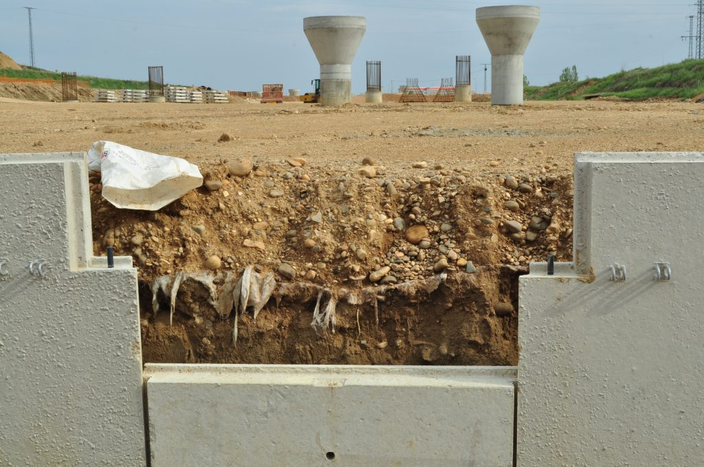 Otra zanja, donde lo destruido ya está siendo tapado por el muro de contención de tierras.