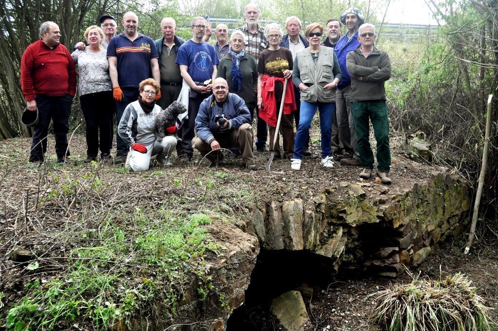 El grupo de ambas asociaciones sobre la alcantarilla descubierta en esta hacendera.