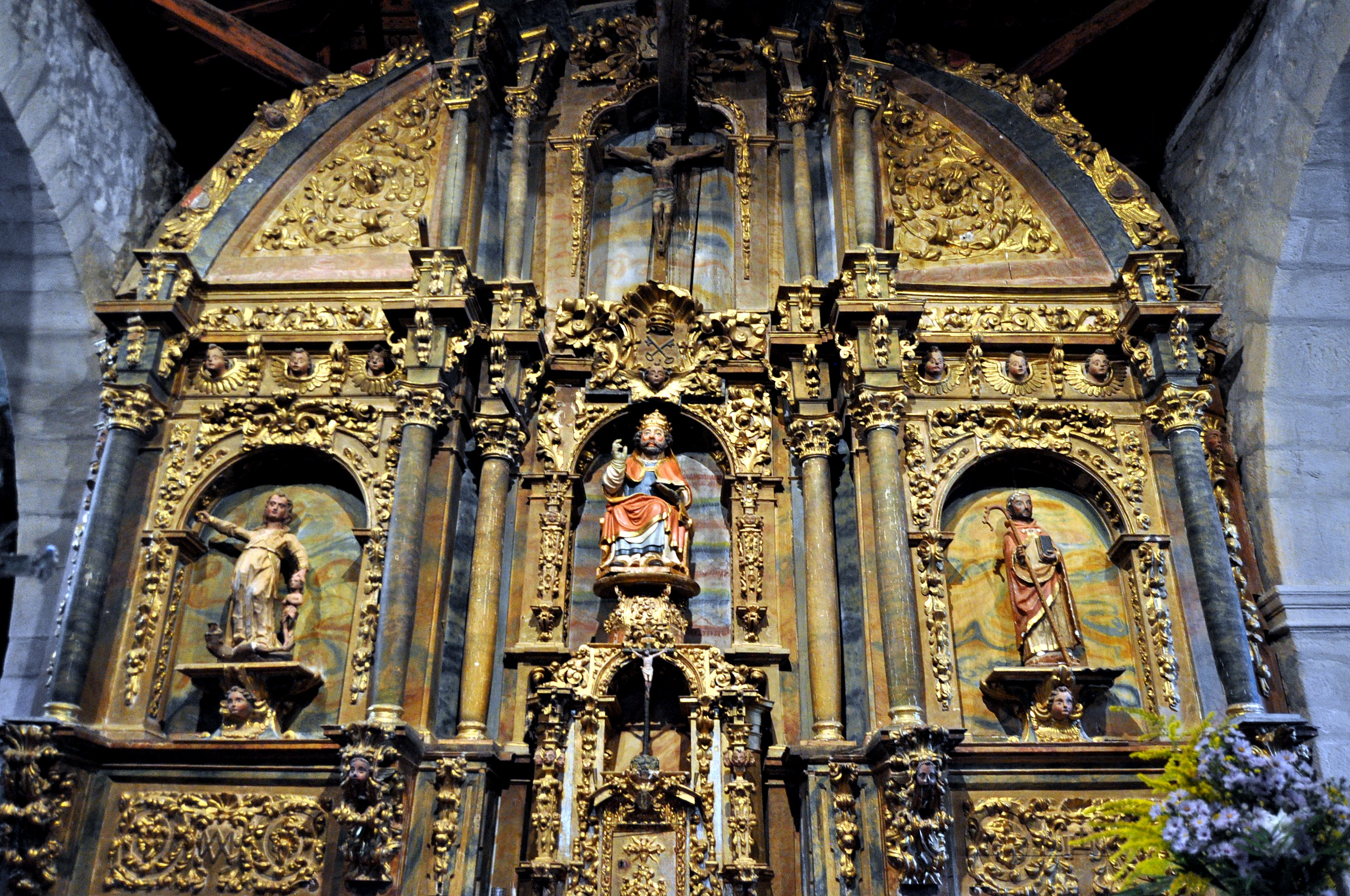 Retablo barroco e imágenes de diversas épocas en la iglesia de San Pedro