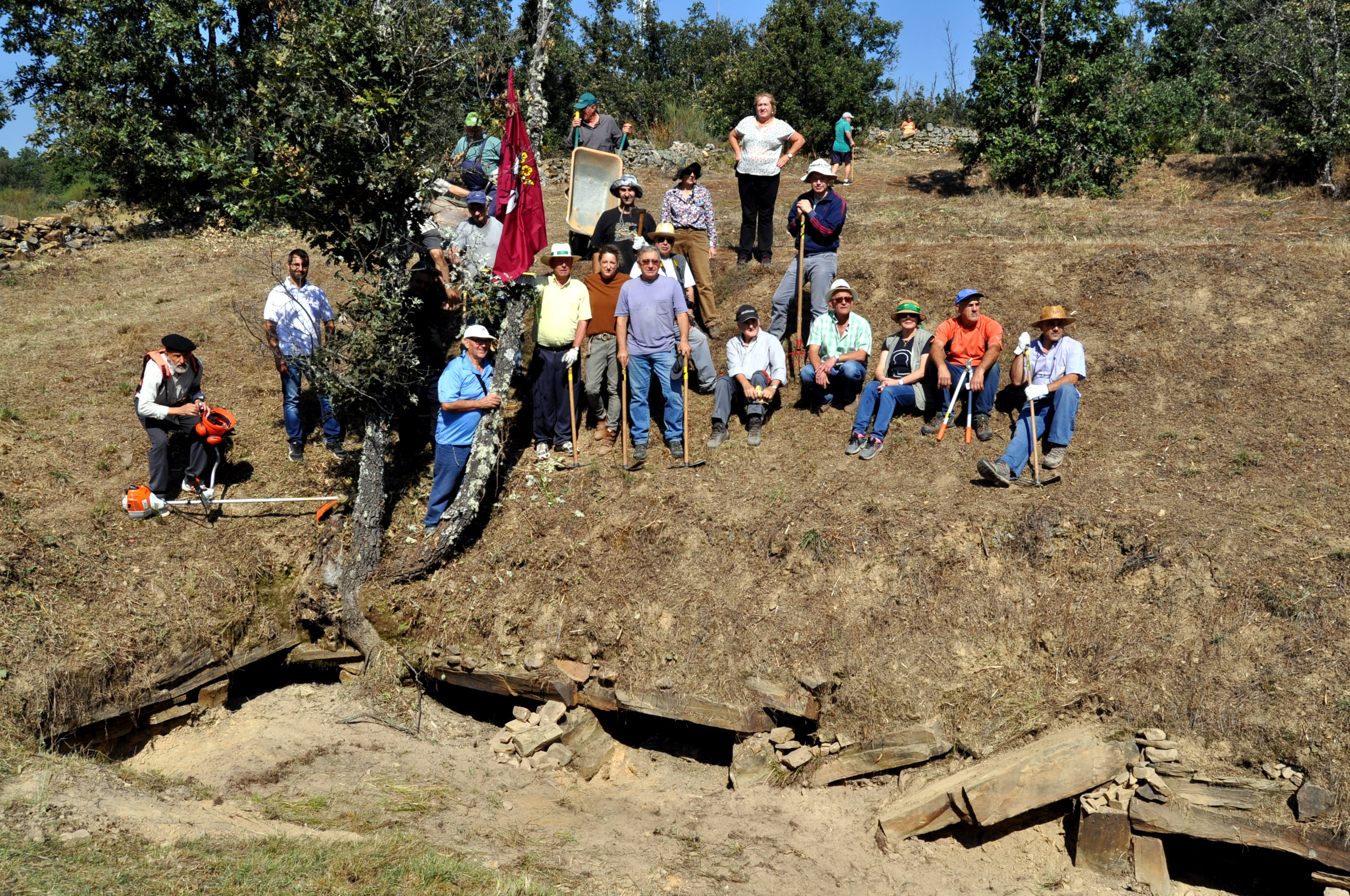 Grupo de voluntarios en el talud de la cámara sepulcral.