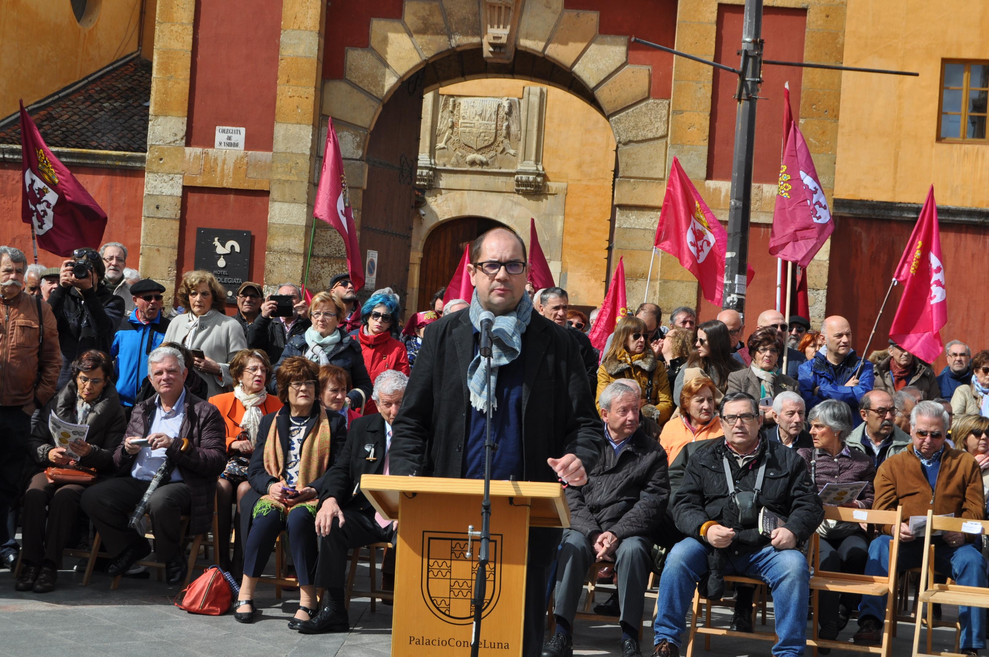Nacho Ares da paso a los intervinientes. Detrás, Marcelino Fernández, presidente de promonumenta y algunas personas portando banderas de León.