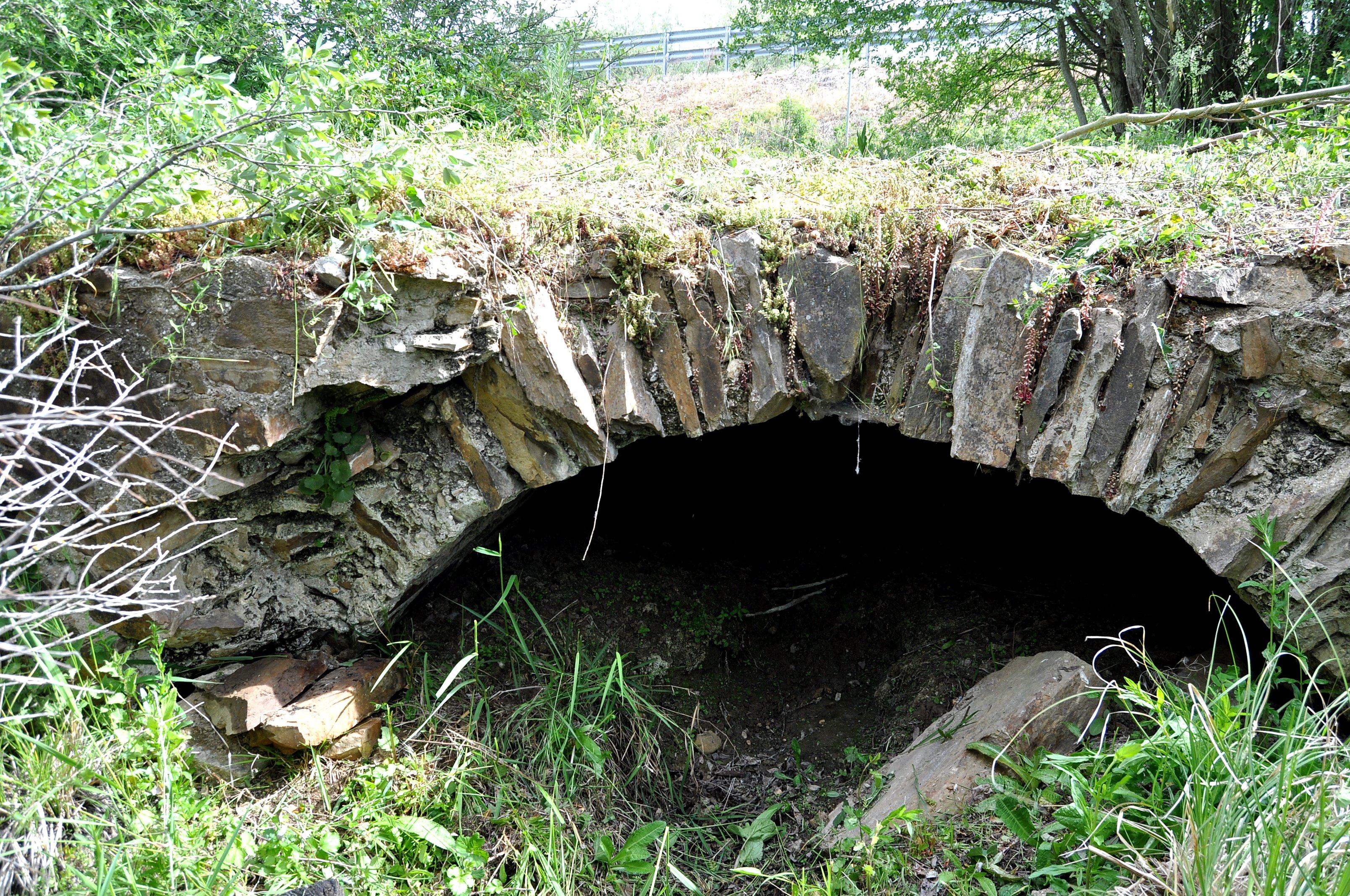 Alcantarilla con bóveda de lajas de piedra, protegida por el murete lateral (caído)
